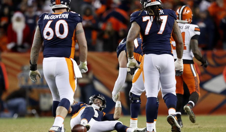 Denver Broncos quarterback Case Keenum is helped up by teammates after being sacked on fourth down during the second half of an NFL football game against the Cleveland Browns, Saturday, Dec. 15, 2018, in Denver. The Browns won 17-16. (AP Photo/Jack Dempsey)