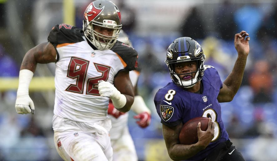 Baltimore Ravens quarterback Lamar Jackson, right, rushes past Tampa Bay Buccaneers defensive tackle William Gholston in the second half of an NFL football game, Sunday, Dec. 16, 2018, in Baltimore. (AP Photo/Gail Burton)
