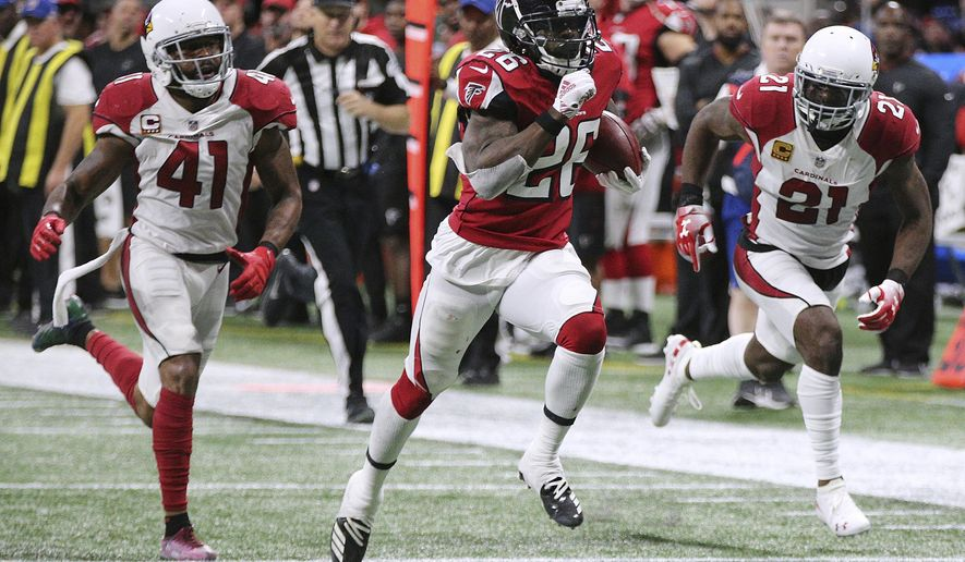 Atlanta Falcons running back Tevin Coleman breaks away from Arizona Cardinals defenders Antoine Bethea, left, and Patrick Peterson for a long touchdown run during the third quarter of an NFL football game on Sunday, Dec 16, 2018, in Atlanta. (Curtis Compton/Atlanta Journal-Constitution via AP)
