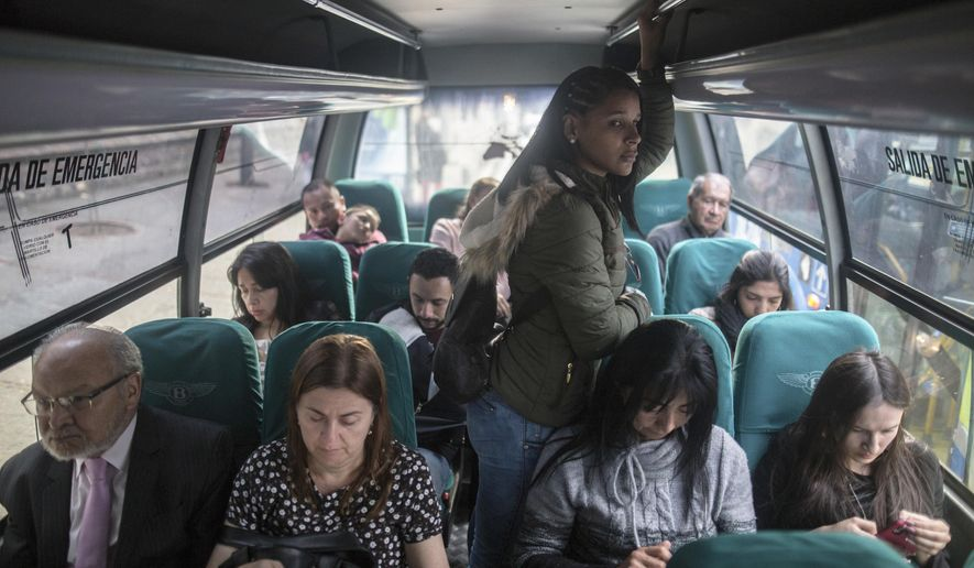 In this Dec. 11, 2018 photo, Venezuelan migrant Emili Espinoza commutes back home after a day's work at a health food restaurant in Bogota, Colombia. Like thousands of other Venezuelans migrating in the largest exodus in Latin America's modern history, Espinoza made an agonizing choice: To leave without her three children. (AP Photo/Ivan Valencia)