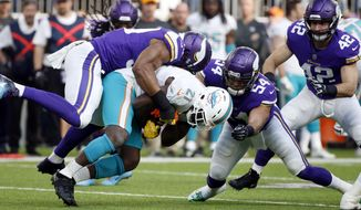Miami Dolphins running back Frank Gore (21) is tackled by Minnesota Vikings defensive end Danielle Hunter, left, and middle linebacker Eric Kendricks (54) during the first half of an NFL football game, Sunday, Dec. 16, 2018, in Minneapolis. (AP Photo/Bruce Kluckhohn)