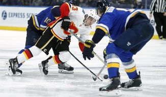 Calgary Flames' Johnny Gaudreau (13) falls between St. Louis Blues' Brayden Schenn (10) and Jay Bouwmeester, right, during the third period of an NHL hockey game Sunday, Dec. 16, 2018, in St. Louis. (AP Photo/Jeff Roberson)