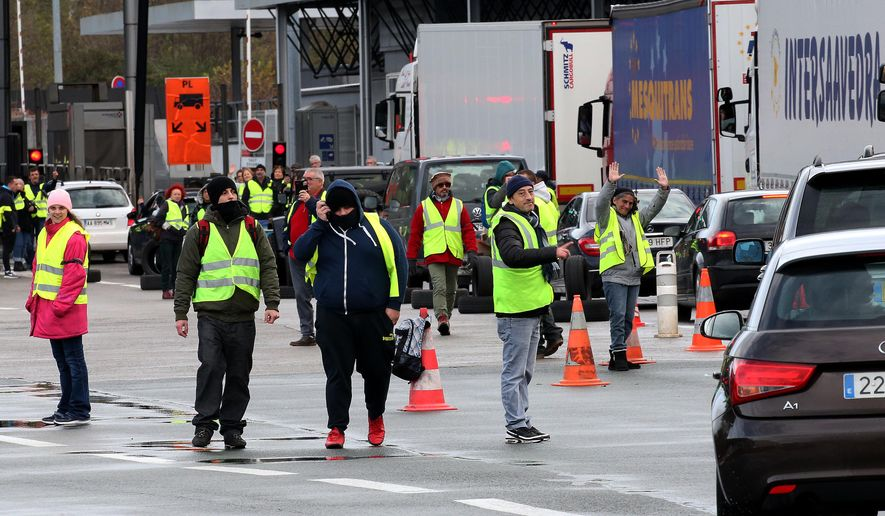 "Demonstrators wearing yellow vests on the blocked highway near the French border with Spain, during a protest Saturday, Dec. 15, 2018 in Biriatou, southwestern France. Police have deployed in large numbers Saturday for the fifth straight weekend of demonstrations by the ""yellow vest"" protesters, with authorities repeating calls for calm after protests on previous weekends turned violent. (AP Photo/Bob Edme)"