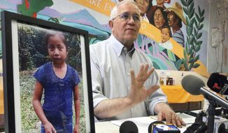 Annunciation House director Ruben Garcia answers questions from the media after reading a statement from the family of Jakelin Caal Maquin, pictured at left, during a press briefing at Casa Vides, Saturday, Dec. 15, 2018, in downtown El Paso, Texas. Maquin had received her first pair of shoes several weeks ago, when her father said they would set out together for the U.S., thousands of miles from her impoverished Guatemalan village. Instead she died in a Texas hospital two days after being taken into custody by U.S. Border Patrol agents in a remote stretch of New Mexico desert. (Rudy Gutierrez/The El Paso Times via AP) **FILE**