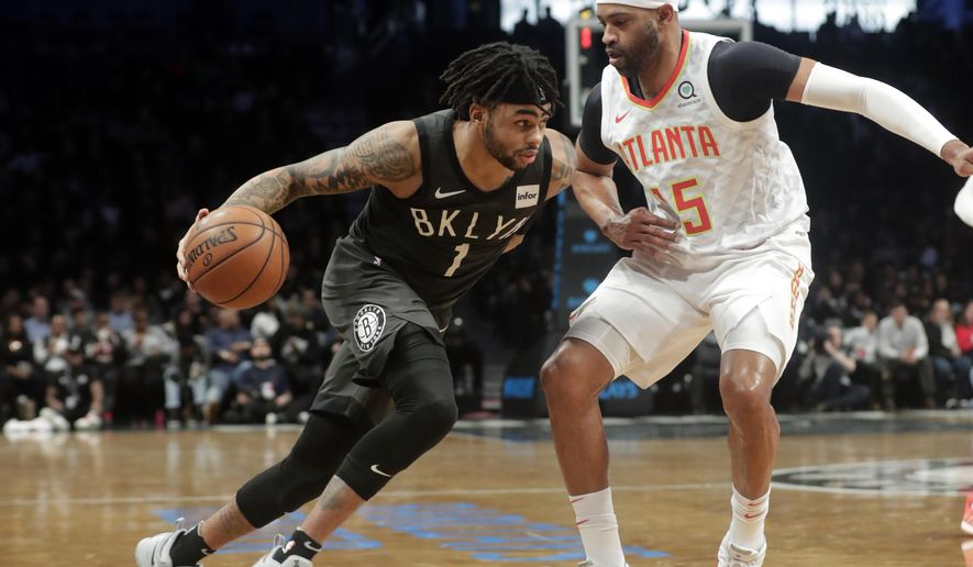 Brooklyn Nets' D'Angelo Russell (1) drives past Atlanta Hawks' Vince Carter (15) during the second half of an NBA basketball game Sunday, Dec. 16, 2018, in New York. The Nets won 144-127. (AP Photo/Frank Franklin II)