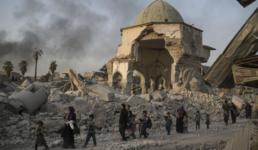 FILE - In this July 4, 2017, file photo, fleeing Iraqi civilians walk past the heavily damaged al-Nuri mosque as Iraqi forces continue their advance against Islamic State militants in Iraq's Old City of Mosul. Iraqi religious leaders have laid the cornerstone to rebuild Mosul's landmark al-Nuri mosque, which was blown up in the battle with Islamic State militants in 2017. (AP Photo/Felipe Dana, File)