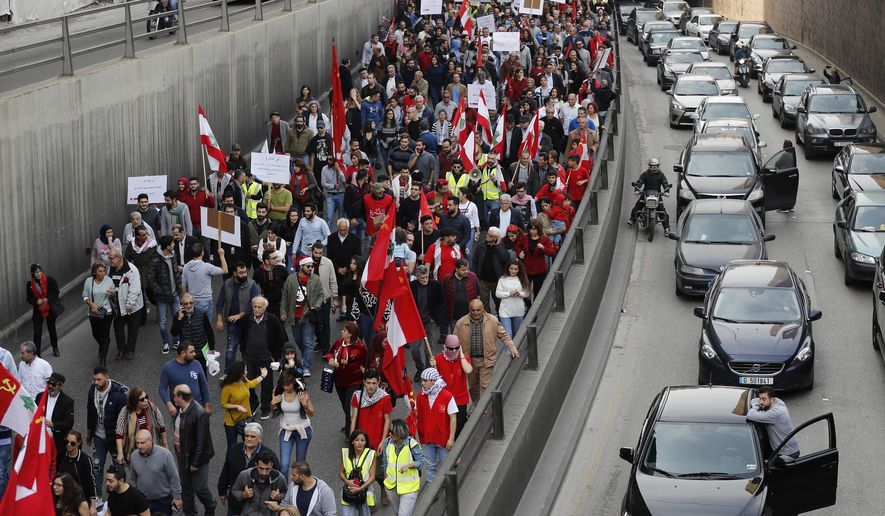 People stand outside their cars watching an anti-government march organized by the country's communist party, in Beirut, Lebanon, Sunday, Dec. 16, 2018. Hundreds of Lebanese called for an end to a stalemate over forming a government seven months after elections. The Sunday protests were organized by the country's vibrant communist party, but drew others frustrated by the country's deepening economic and political crisis. (AP Photo/Hussein Malla)