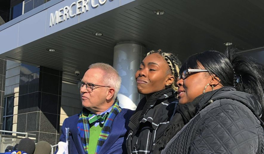 """FILE - In this Dec. 12, 2018, file photo, Jazmine Headley, center, joins attorney Brian Neary and her mother, Jacqueline Jenkins, outside a courthouse in Trenton, N.J., after she accepted a deal to enter a pretrial intervention program related to credit card theft charges she faced. Headley, who had her toddler yanked from her arms by New York police in a widely seen video said in an interview published on Sunday that she went into """"defense mode."""" (AP Photo/Mike Catalini, File)"""