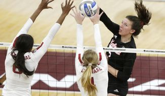 Nebraska's Mikaela Foecke (2) hits on the block of Stanford's Tami Alade (8) and Jenna Gray (1) in the first set of the championship match of the NCAA Div I Women's Volleyball Championships, Saturday, Dec. 15, 2018, in Minneapolis. (AP Photo/Andy Clayton-King)