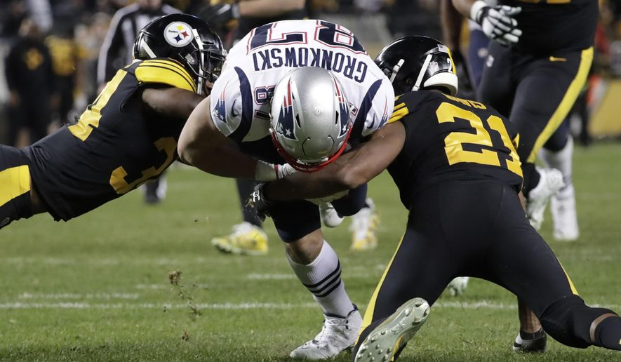 New England Patriots tight end Rob Gronkowski (87) is tackled by Pittsburgh Steelers free safety Sean Davis (21) and Coty Sensabaugh (24) during the second half of an NFL football game in Pittsburgh, Sunday, Dec. 16, 2018. (AP Photo/Don Wright)