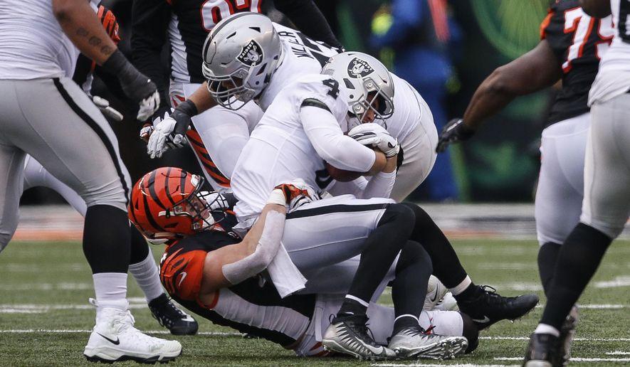 Oakland Raiders quarterback Derek Carr (4) is sacked by Cincinnati Bengals defensive end Sam Hubbard in the first half of an NFL football game, Sunday, Dec. 16, 2018, in Cincinnati. (AP Photo/Gary Landers)
