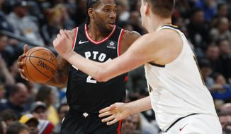 Toronto Raptors forward Kawhi Leonard, back, looks to pass the ball as Denver Nuggets center Nikola Jokic defends in the first half of an NBA basketball game Sunday, Dec. 16, 2018, in Denver. (AP Photo/David Zalubowski)