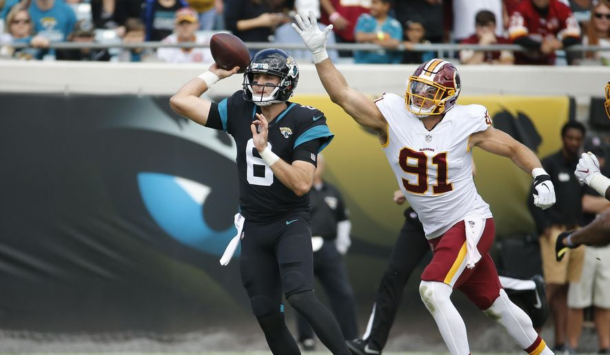 Washington Redskins outside linebacker Ryan Kerrigan (91) tries to stop Jacksonville Jaguars quarterback Cody Kessler (6) from throwing a pass during the first half of an NFL football game, Sunday, Dec. 16, 2018, in Jacksonville, Fla. (AP Photo/Stephen B. Morton) **FILE**