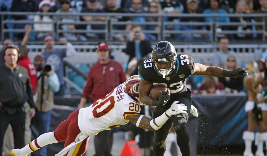 Washington Redskins strong safety Ha Ha Clinton-Dix (20) stops Jacksonville Jaguars running back David Williams (33) after a short gain during the second half of an NFL football game, Sunday, Dec. 16, 2018, in Jacksonville, Fla. (AP Photo/Stephen B. Morton)