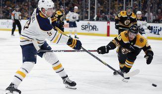 Buffalo Sabres' Jack Eichel (9) shoots past Boston Bruins' Matt Grzelcyk (48) to score against Tuukka Rask during the third period of an NHL hockey game in Boston, Sunday, Dec. 16, 2018. (AP Photo/Michael Dwyer)