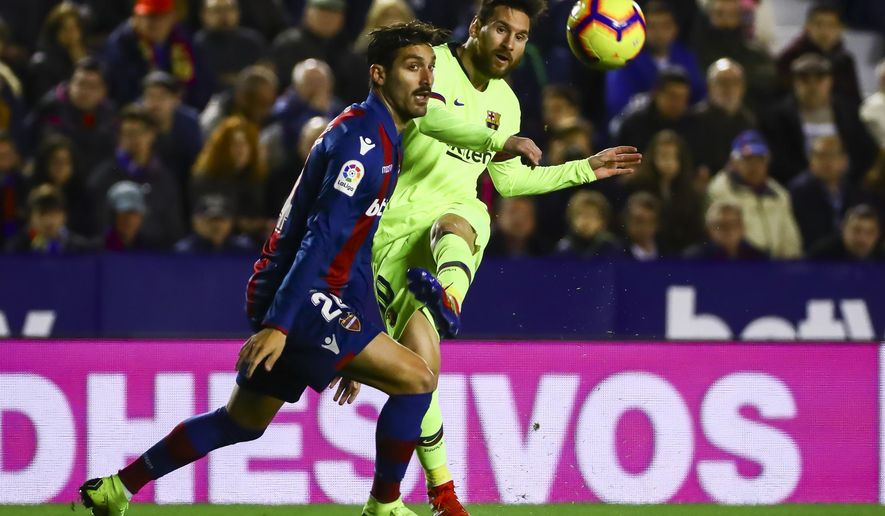 Levante's defender Jose Gomez Campana, left, in action against FC Barcelona's forward Lionel Messi, right, during their La Liga soccer match between Levante UD and FC Barcelona at Ciutat de Valencia stadium in Valencia, Spain, Sunday, Dec. 16, 2018.  (AP Photo/Jose Miguel Fernandez de Velasco)