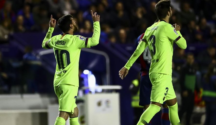 FC Barcelona's forward Lionel Messi, left, celebrate after scoring the 0-4 goal with his teammate FC Barcelona's defender Gerard Pique, right, during their La Liga soccer match between Levante UD and FC Barcelona at Ciutat de Valencia stadium in Valencia, Spain, Sunday, Dec. 16, 2018. (AP Photo/Jose Miguel Fernandez de Velasco)