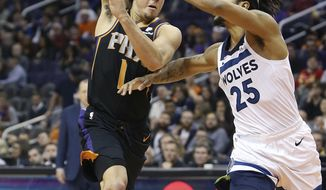 Phoenix Suns guard Devin Booker (1) makes a no-look pass over the defense of Minnesota Timberwolves' Derrick Rose during the second half of an NBA basketball game, Saturday, Dec. 15, 2018, in Phoenix. (AP Photo/Ralph Freso)