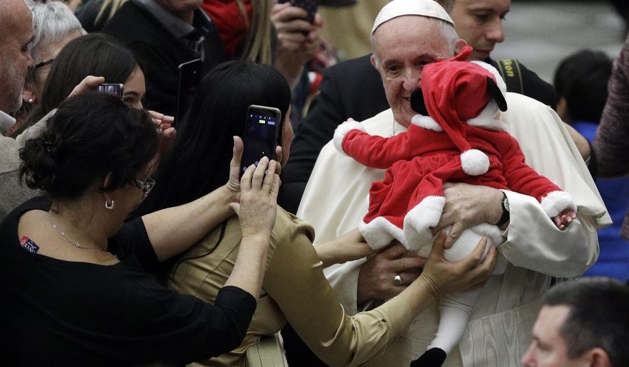 Pope Francis hugs a baby dressed as Santa Claus during audience with children and family from the dispensary of Santa Marta, a Vatican charity that offers special help to mothers and children in need, in the Paul VI hall at the Vatican, Sunday, Dec. 16, 2018. (AP Photo/Gregorio Borgia)
