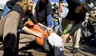 Protestors demonstrate the use of water boarding to volunteer Maboud Ebrahim Zadeh, Monday, Nov. 5, 2007, in front of the Justice Department in Washington. The demonstration was to highlight the use of water boarding as torture, to protest the nomination of Attorney General-designate Michael Mukasey. (AP Photo/Manuel Balce Ceneta)