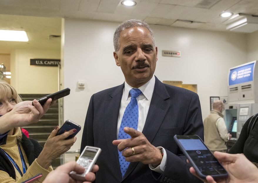 Former Attorney General Eric Holder takes questions from reporters at the Capitol where he attended the swearing-in of Sen. Doug Jones, D-Ala., in Washington, Wednesday, Jan. 3, 2018. (AP Photo/J. Scott Applewhite)