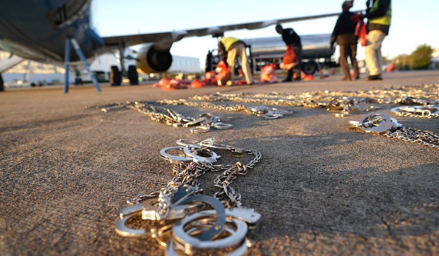 In this Friday, Nov. 16, 2018, photo, restraints lie on the tarmac as personal belongings of immigrants who entered the United States illegally are loaded onto a plane for a deportation flight to El Salvador by U.S. Immigration and Customs Enforcement in Houston. An obscure division of U.S. Immigration and Customs Enforcement operates hundreds of flights each year to remove immigrants. (AP Photo/David J. Phillip)