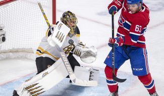 Boston Bruins goaltender Jaroslav Halak (41) stops Montreal Canadiens centre Matthew Peca (63) during third period NHL hockey action in Montreal on Monday, Dec. 17, 2018. (Ryan Remiorz/The Canadian Press via AP)