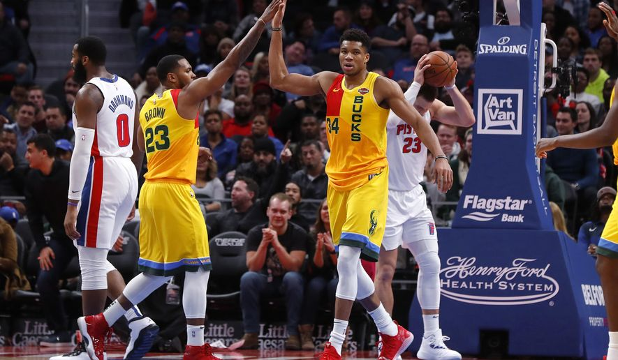 Milwaukee Bucks forward Giannis Antetokounmpo (34) celebrates a basket with Sterling Brown (23) in the second half of an NBA basketball game against the Detroit Pistons in Detroit, Monday, Dec. 17, 2018. (AP Photo/Paul Sancya)