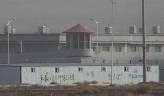 "In this Monday, Dec. 3, 2018, photo, a guard tower and barbed wire fences are seen around a facility in the Kunshan Industrial Park in Artux in western China's Xinjiang region. This is one of a growing number of internment camps in the Xinjiang region, where by some estimates 1 million Muslims are detained, forced to give up their language and their religion and subject to political indoctrination. Now, the Chinese government is also forcing some detainees to work in manufacturing, food and service industries, in what activists call ""black factories."" (AP Photo/Ng Han Guan)"