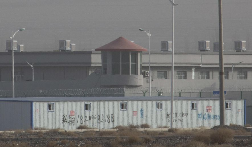 """In this Monday, Dec. 3, 2018, photo, a guard tower and barbed wire fences are seen around a facility in the Kunshan Industrial Park in Artux in western China's Xinjiang region. This is one of a growing number of internment camps in the Xinjiang region, where by some estimates 1 million Muslims are detained, forced to give up their language and their religion and subject to political indoctrination. Now, the Chinese government is also forcing some detainees to work in manufacturing, food and service industries, in what activists call """"black factories."""" (AP Photo/Ng Han Guan)"""