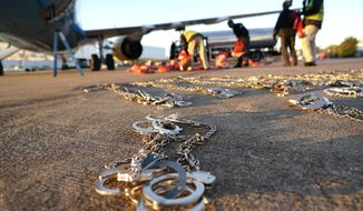 In this Friday, Nov. 16, 2018, photo, restraints lie on the tarmac as personal belongings of immigrants who entered the United States illegally are loaded onto a plane for a deportation flight to El Salvador by U.S. Immigration and Customs Enforcement in Houston. An obscure division of U.S. Immigration and Customs Enforcement operates hundreds of flights each year to remove immigrants. (AP Photo/David J. Phillip) **FILE**