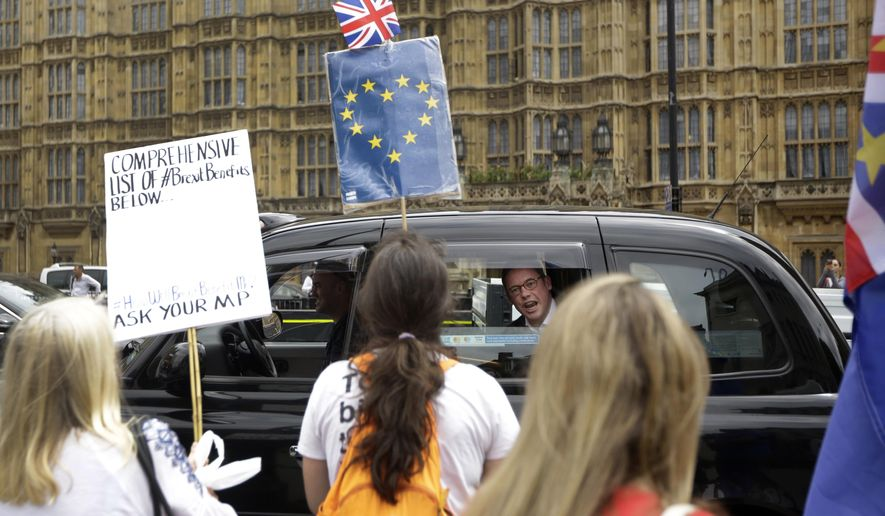 FILE - In this Wednesday, June 20, 2018 file photo, a man in a passing taxi shouts his disagreement at anti-Brexit, pro-EU supporters protesting backdropped by the Houses of Parliament in London. The divisions opened up by the 2016 referendum have not healed, but hardened, splitting Britain into two camps: leavers and remainers. Almost the only thing the two groups share is pessimism about the way Brexit is going. (AP Photo/Matt Dunham)