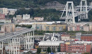 FILE - In this Tuesday, Aug. 14, 2018 file photo cars are blocked on the Morandi highway bridge after a section of it collapsed, in Genoa, northern Italy. A large section of the bridge collapsed over an industrial area in the Italian city of Genova during a sudden and violent storm, leaving vehicles crushed in rubble below. (AP Photo/Antonio Calanni, File)