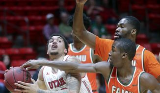 Utah forward Timmy Allen (20) looks to make a shot as Florida A&M guard Justin Ravenel (21) guards him during an NCAA college basketball game at the Huntsman Center in Salt Lake City on Monday, Dec. 17, 2018. (Kristin Murphy/The Deseret News via AP)