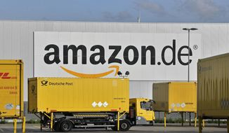 In this file photo dated Wednesday, Nov. 14, 2018, post trucks leave the Amazon Logistic Center in Rheinberg, Germany. Workers at two Amazon distribution centers in Germany have gone on strike as part of a push for improved work conditions, leading to fears that Christmas orders may not arrive in time. (AP Photo/Martin Meissner, file)