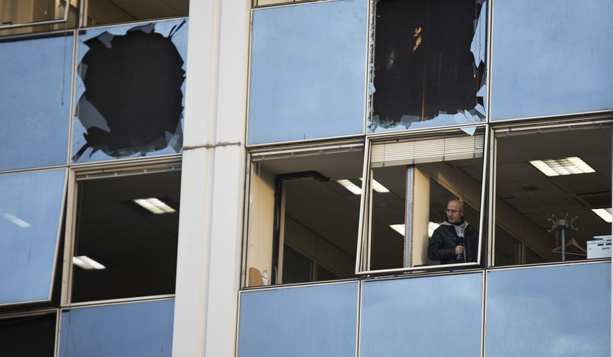 A journalist looks out a broken window after a powerful bomb exploded outside private Greek television station Skai, in Faliro, Athens, on Monday, Dec, 17, 2018. Police said the blast occurred outside the broadcasters' headquarters near Athens after telephoned warnings prompted authorities to evacuate the building, causing extensive damage but no injuries. (AP Photo/Petros Giannakouris)