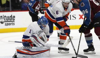 New York Islanders goaltender Thomas Greiss, left, stops a shot off the stick of Colorado Avalanche right wing Mikko Rantanen, right, as New York defenseman Ryan Pulock covers in the first period of an NHL hockey game Monday, Dec. 17, 2018, in Denver. (AP Photo/David Zalubowski)