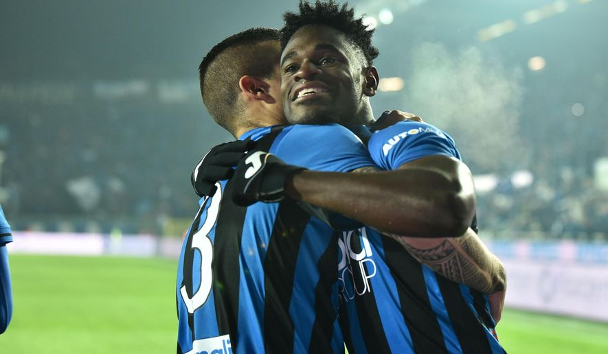 Atalanta's Duvan Zapata, right, is embraced by a teammate after scoring his team's opening goal during the Italian Serie A soccer match between Atalanta and Lazio at the Atleti Azzurri d'Italia stadium in Bergamo, Italy, Monday, Dec. 17 2018. (Paolo Magni/ANSA via AP)