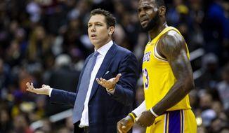 Los Angeles Lakers forward LeBron James (23) and head coach Luke Walton dispute a call during the first half of an NBA basketball game against the Washington Wizards, Sunday, Dec. 16, 2018, in Washington. (AP Photo/Al Drago)