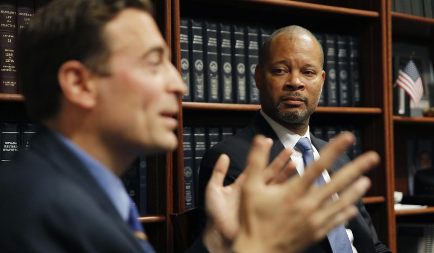 Nevada's incoming Democratic Attorney General Aaron, right, listens as outgoing Republican Attorney General Adam Laxalt speaks attend a news conference, Monday, Dec. 17, 2018, in Las Vegas. (AP Photo/John Locher)