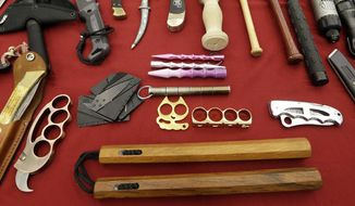 FILE - In this April 6, 2017, file photo, objects confiscated from passengers' carry-on luggage, including nunchucks, bottom, are displayed at Seattle-Tacoma International Airport in SeaTac, Wash. A federal court says New York's ban on nunchucks, the martial arts weapon made famous by Bruce Lee but prohibited in the state for decades, is unconstitutional under the Second Amendment. (AP Photo/Elaine Thompson, File)