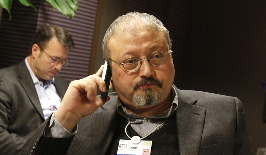 In this Jan. 29, 2011, file photo, Saudi Arabian journalist Jamal Khashoggi speaks on his cellphone at the World Economic Forum in Davos, Switzerland. Saudi Arabia issued an unusually strong rebuke of the U.S. Senate on Monday, Dec. 17, 2018, rejecting a bipartisan resolution that put the blame for the killing of Saudi journalist Jamal Khashoggi squarely on the Saudi crown prince and describing it as interference in the kingdom's affairs. (AP Photo/Virginia Mayo, File)