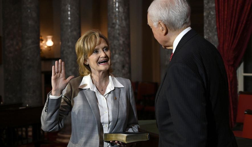 Sen. Cindy Hyde-Smith, R-Miss., left, stands with Sen. Orrin Hatch, R-Utah, right, during a ceremonial swearing-in on Capitol Hill in Washington, Monday, Dec. 17, 2018. (AP Photo/Susan Walsh)