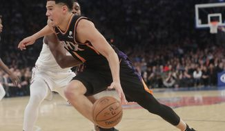 Phoenix Suns' Austin Rivers (1) drives past New York Knicks' Emmanuel Mudiay (1) during the first half of an NBA basketball game Monday, Dec. 17, 2018, in New York. (AP Photo/Frank Franklin II)