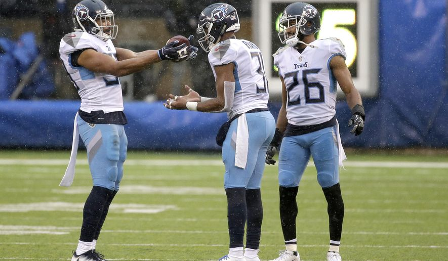 Tennessee Titans inside linebacker Wesley Woodyard, left, celebrates after free safety Kevin Byard, center, intercepted a pass from New York Giants quarterback Eli Manning, not pictured, during the second half of an NFL football game, Sunday, Dec. 16, 2018, in East Rutherford, N.J. Titans cornerback Logan Ryan (26) looks on during the celebration. (AP Photo/Seth Wenig)