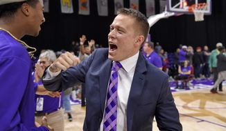 Furman head coach Bob Richey, right, celebrates his team's win with fans after an NCAA college basketball game against North Carolina Wilmington, Saturday, Dec. 15, 2018, in Greenville, S.C. (AP Photo/Richard Shiro)