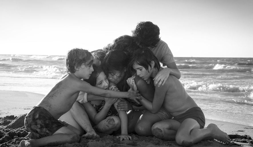 "This image released by Netflix shows Yalitza Aparicio, center, in a scene from the film ""Roma,"" by filmmaker Alfonso Cuaron. (Carlos Somonte/Netflix via AP)"