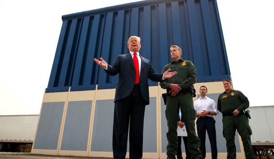 President Trump joins Border Patrol San Diego sector chief Rodney Scott before a prototype unit of the border wall just outside San Diego. (Associated Press)