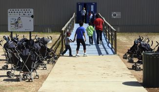 """In this Thursday, Aug. 9, 2018, photo, provided by U.S. Immigration and Customs Enforcement, immigrants walk into a building at South Texas Family Residential Center in Dilley, Texas. Currently housing 1,520 mothers and their children, about 10 percent are families who were temporarily separated and then reunited under a """"zero tolerance policy"""" that has since been reversed. (Charles Reed/U.S. Immigration and Customs Enforcement via AP)"""