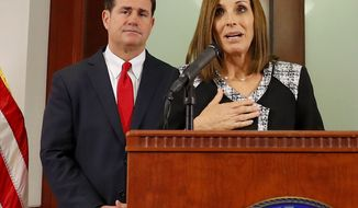 U.S. Rep. Martha McSally, R-Ariz., speaks, during a news conference Tuesday, Dec. 18, 2018, at the Capitol in Phoenix, after Arizona Gov. Doug Ducey, rear, announced his decision to replace U.S. Sen. Jon Kyl, R-Ariz. with McSally in the U.S. Senate seat that belonged to Sen. John McCain. McSally will take over after Kyl's resignation becomes effective Dec. 31. (AP Photo/Matt York)